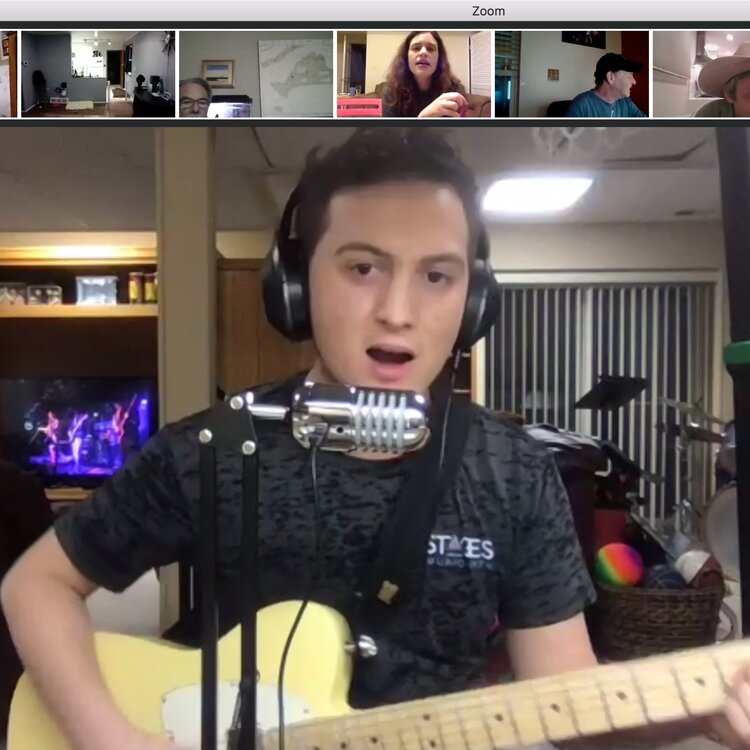 Boy sings and plays electric guitar during a virtual lesson