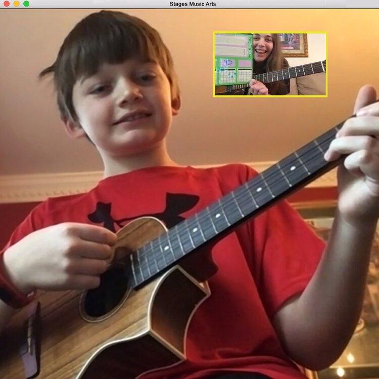 Boy plays guitar during a virtual lesson