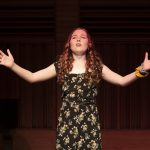 Girl singing with arms outstretched